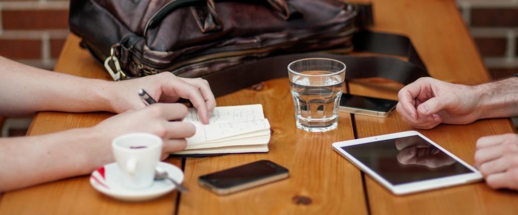 Tisch mit Notizbuch, Kaffeetasse, Wasserglas, Handtasche, Smartphone und Tablett