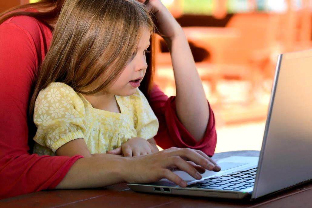 Mutter sitzt mit Kind auf dem Schoß vor einem Laptop